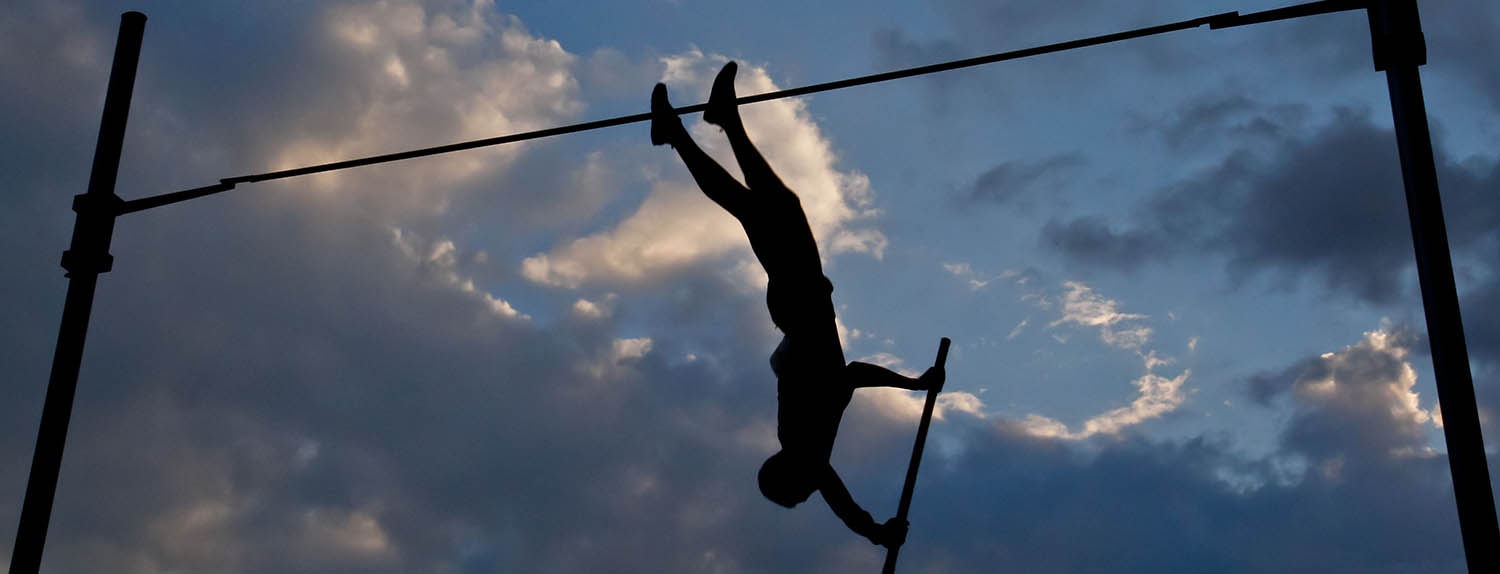 Photo: silhouette of a pole vaulter against a dramatic cloudscape
